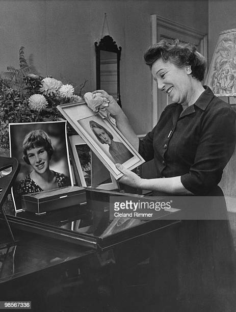 Welsh actress Doris Hare dusting framed photos of her daughters Susan and Kathleen, 14th November 1958.
