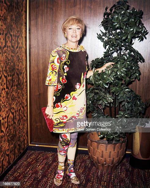 Welsh actress Glynis Johns wearing a dress in an Art Nouveau print with matching tights circa 1965