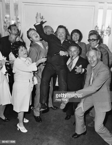 Welsh comedian and singer Harry Secombe is lifted up by his colleagues at a Variety Club of Great Britain luncheon in his honour at the Dorchester...