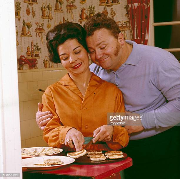 Welsh comedian and singer Harry Secombe pictured with his wife Myra Atherton serving Welsh cakes in a kitchen in 1964