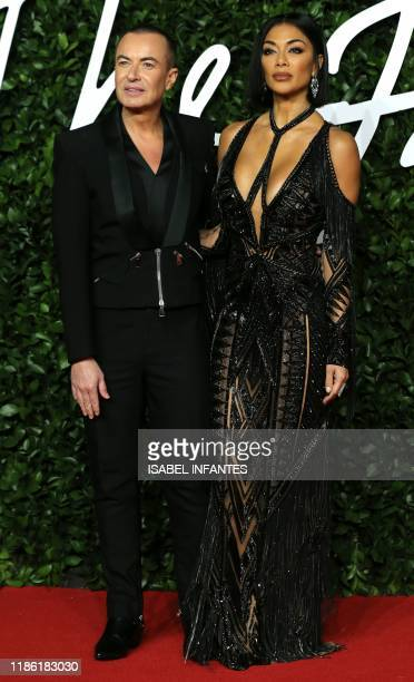 Welsh fashion designer Julien MacDonald and US singer Nicole Scherzinger poses on the red carpet upon arrival at The Fashion Awards 2019 in London on...