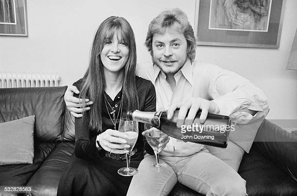 Welsh film and television actor Hywel Bennett shares a bottle of champagne with his bridetobe British broadcaster and journalist Cathy McGowan 1970
