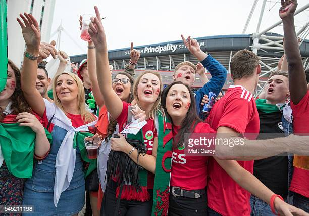 Welsh football fans cheer as they gather outside the Principality Stadium which is showing the Wales v Portugal game on a giant screen on July 6 2016...