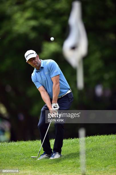 Welsh golfer Bradley Dredge chips on to the 1st green during the final round of the PGA Championship at Wentworth Golf Club in the town of Virginia...
