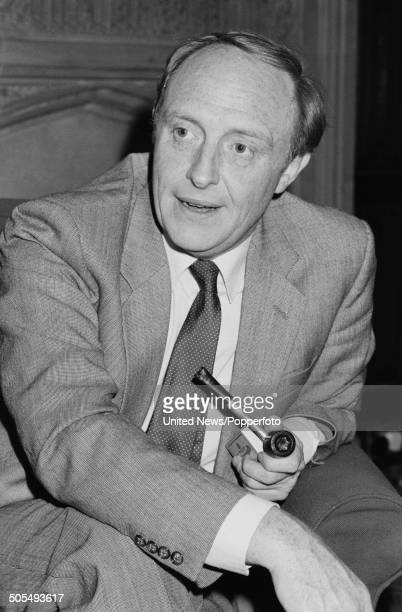 Welsh Labour Party politician and Leader of the Opposition Neil Kinnock pictured being interviewed whilst holding a pipe in the House of Commons in...