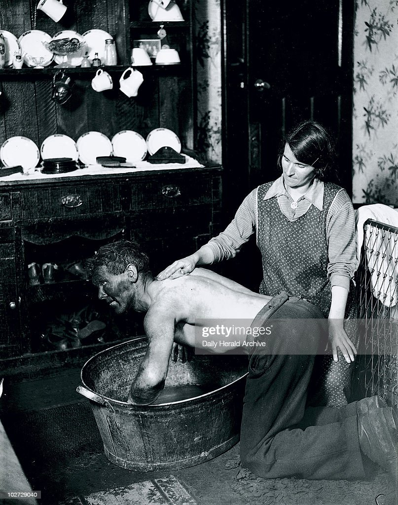 A Welsh miner's wife washing her husband after work, June 1931. Photograph taken by James Jarche for the H V Morton series 'In search of Wales', (1934).