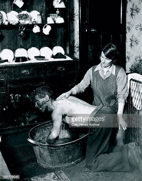 Welsh miner's wife washing her husband after work June 1931 Photograph taken by James Jarche for the H V Morton series 'In search of Wales'