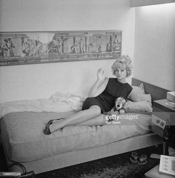 Welsh model and showgirl Mandy RiceDavies smoking a cigarette on a bed UK 26th June 1963