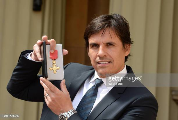 Welsh national team football manager Chris Coleman poses for a photo after he was awarded an OBE by the Prince of Wales during an Investiture...