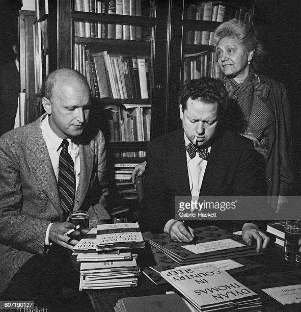 Welsh poet and writer Dylan Thomas signing one of his books for American poet and literary critic John Malcolm Brinnin during a reception held in...