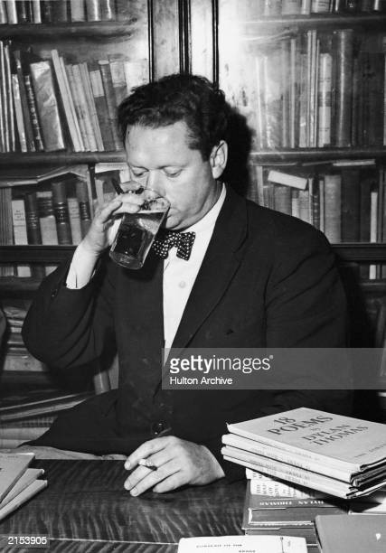 Welsh poet Dylan Thomas drinking a glass of beer and smoking while seated at a desk with stacks of his books of poetry New York City c 1950