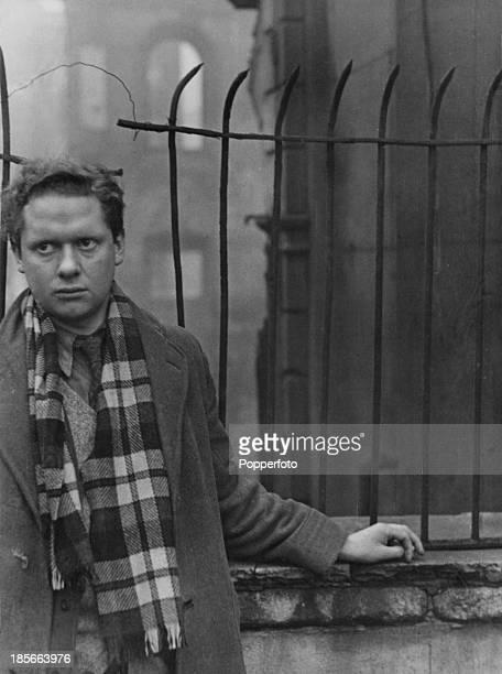 Welsh poet Dylan Thomas standing near bombdamaged buildings in Soho London 1945