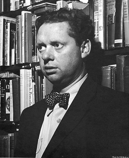Welsh poet Dylan Thomas stands in front of shelves...