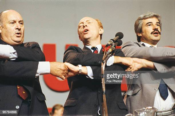 Welsh politician and Labour Party leader Neil Kinnock singing with Party bureaucrats Jim Mortimer and Larry Whitty at the Labour Party Conference in...