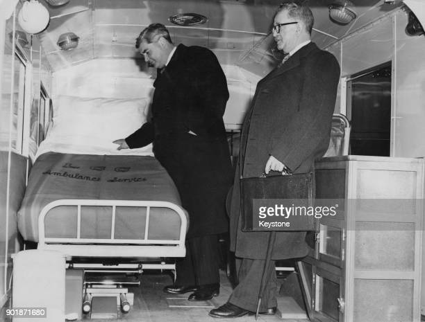 Welsh politician Aneurin Bevan the Minister of Health and H Lord Chairman of the Lancashire Health Committee inspect a swivelling and tilting bed...