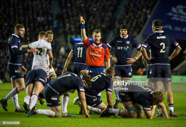 Welsh referee Nigel Owens indicates a penalty for the exhausted Scots in the closing minutes of the 6 Nations clash between Scotland and England at...