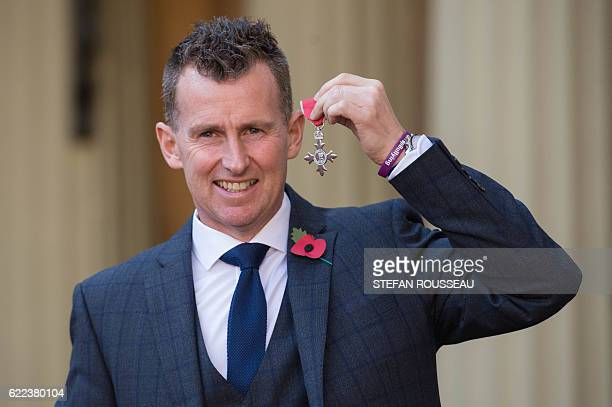 Welsh rugby referee Nigel Owens poses with his insignia after being appointed a Member of the Order of the British Empire at an Investiture ceremony...