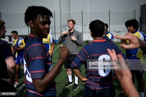 Welsh Rugby Union player Rhys Patchell speaks to local youth rugby players as deaf players sign at the Columbia Heights Education Campus on May 31...