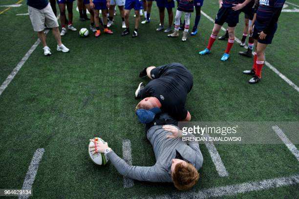 Welsh Rugby Union player Samson Lee demonstrates a tackle on teammate Rhys Patchell while participating in a workshop for youth rugby players at the...
