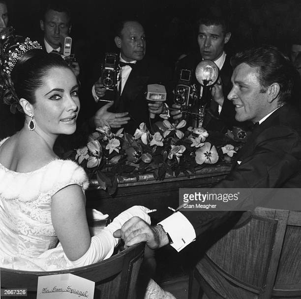 Welsh screen and stage actor Richard Burton and screen actress Elizabeth Taylor with photographers at a screening of David Lean's 'Lawrence of Arabia'