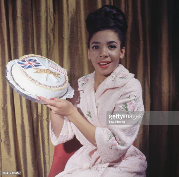Welsh singer Shirley Bassey circa 1965 She is holding a cake decorated with the British and North American flags