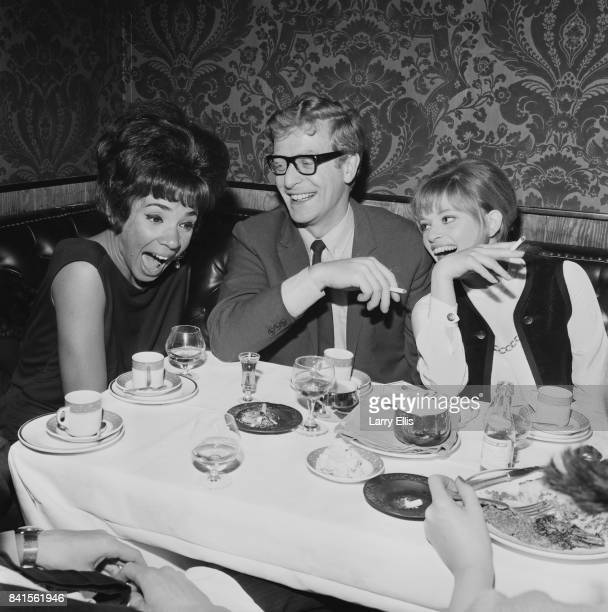 Welsh singer Shirley Bassey English actor Michael Caine and AngloHungarian fashion designer Edina Ronay laugh together while sitting at a table at...