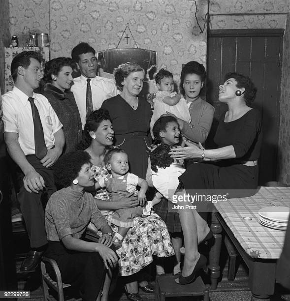 Welsh singer Shirley Bassey singing to members of her family at their home in the Tiger Bay area of Cardiff, Wales, 9th December 1955.