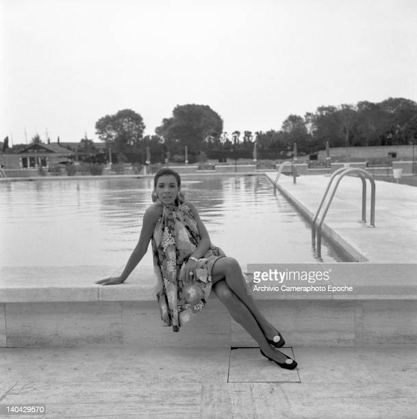 Welsh singer Shirley Bassey sitting on the edge of a swimming pool 1970s