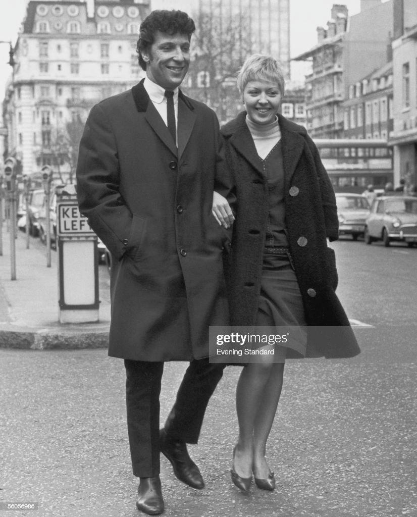 Welsh singer Tom Jones and his wife Linda walking down a street, 1965.
