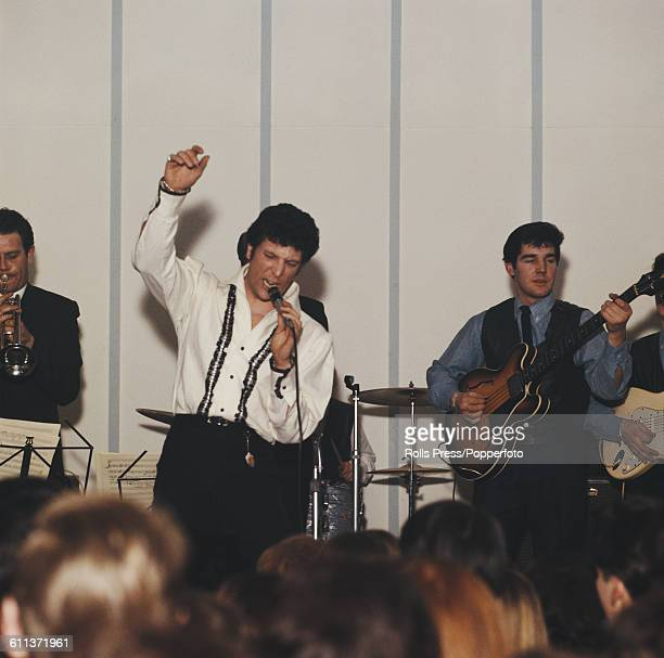 Welsh singer Tom Jones performs on stage in front of an audience with backing band behind circa 1965