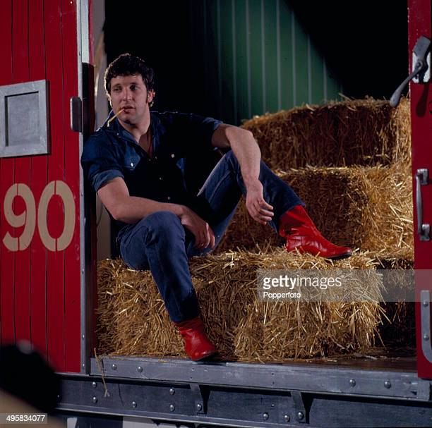 Welsh singer Tom Jones posed wearing denim shirt and jeans and red leather boots inside a boxcar on the set of his television series 'The Tom Jones...