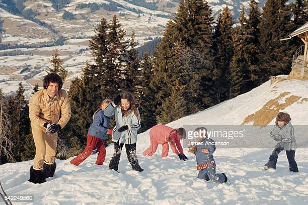 Welsh singer Tom Jones throws snowballs with his three daughters and their friends during a family winter vacation
