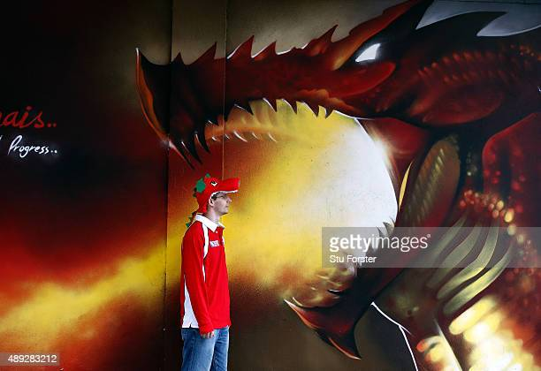 Welsh supporter stands beside a dragon mural before the 2015 Rugby World Cup Pool A match between Wales and Uruguay at Millennium Stadium on...