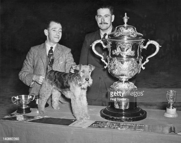Welsh Terrior bitch Twynstar Dyma-Fi with her handler G. M. Barr and owner Captain I. M. Thomas, after winning Best In Show at the Crufts...