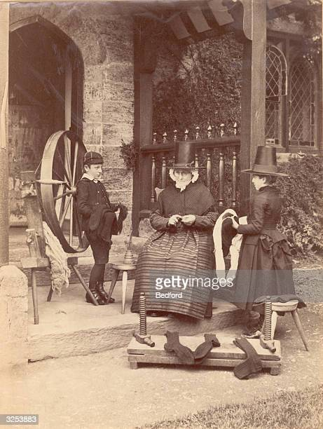 Welsh woman and her children, from Bettws-y-Coed, spinning.