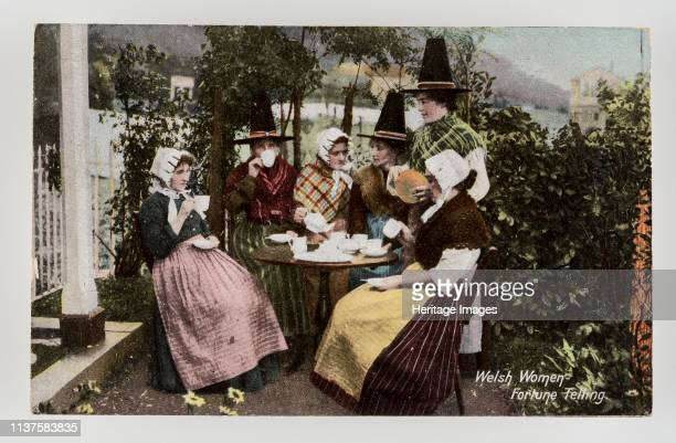 Welsh women fortune telling'. C1900s. Produced between about 1900 and the beginning of the First World War. Group of six Welsh women around a tea...