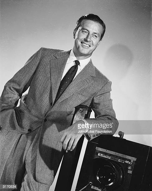 Welsh-born actor Ray Milland leans against a camera with a confident smile on his face.