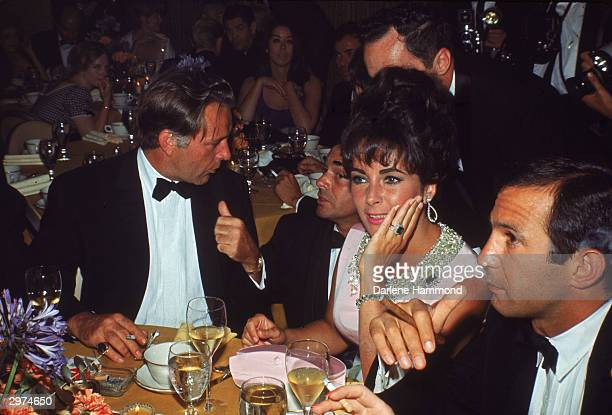 Welsh-born actor Richard Burton , his wife, British-born actress Elizabeth Taylor, and American actor Ben Gazzara talk with friends at the premiere...