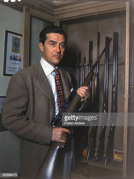 Welshborn American actor Ray Milland holds a gun as he stands in front of a glassdoored gun rack 1940s On the wall behind his is a framed poster that...