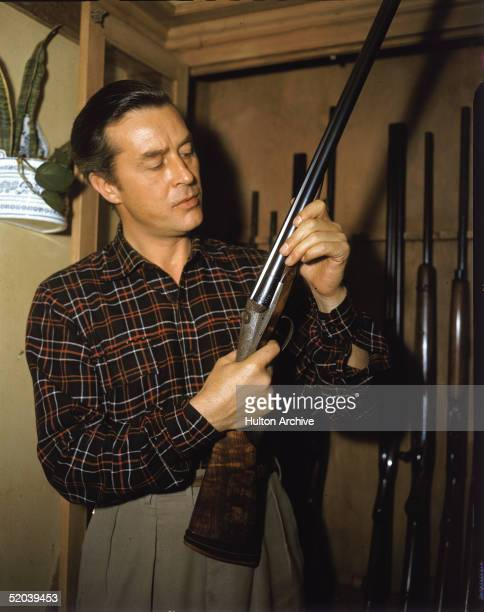 Welshborn American actor Ray Milland holds up a gun as he stands in front of a gun rack 1950s