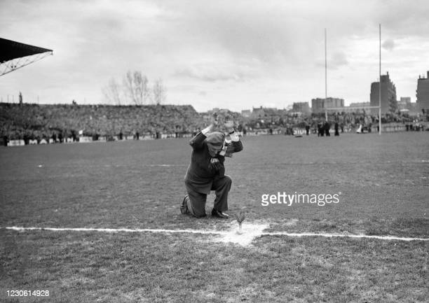 Welshman plants a leek, his country's emblem, in the middle of the field of the Colombes stadium, on March 26, 1955 before the match between France...