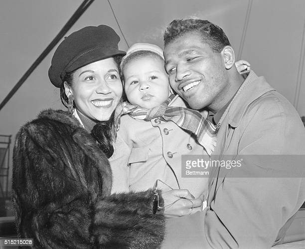 Welterweight boxing champion Sugar Ray Robinson and his wife, Edna Mae, say hello to their son, one-year-old Ray Robinson Jr., as they arrive aboard...
