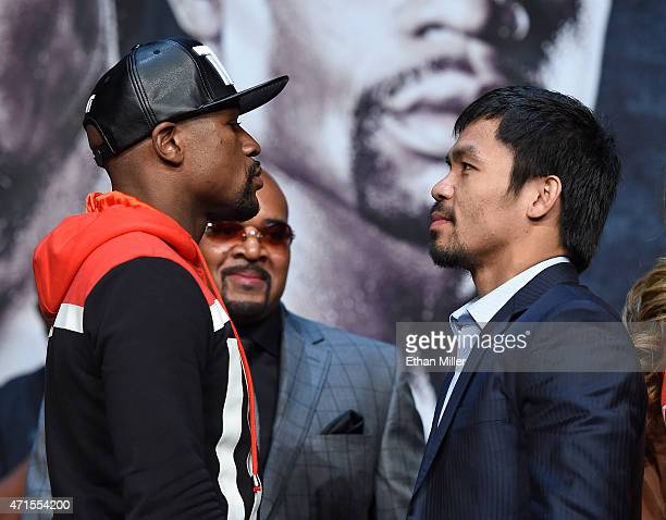 WBA welterweight champion Floyd Mayweather Jr and WBO welterweight champion Manny Pacquiao face off during a news conference at the KA Theatre at MGM...