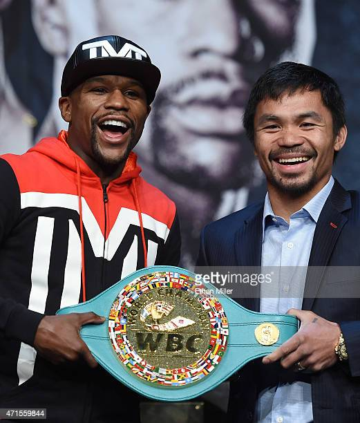 WBA welterweight champion Floyd Mayweather Jr and WBO welterweight champion Manny Pacquiao pose with a WBC championship belt during a news conference...