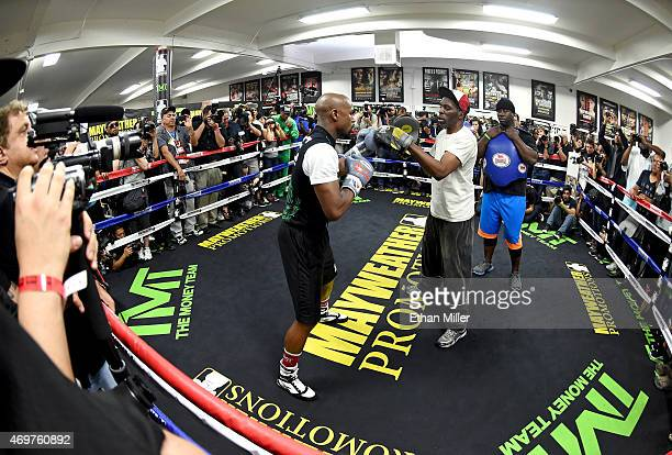 WBC/WBA welterweight champion Floyd Mayweather Jr works out with his uncle Roger Mayweather as cotrainer Nate Jones looks on at the Mayweather Boxing...