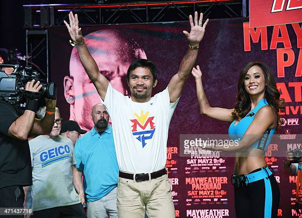 Welterweight champion Manny Pacquiao arrives at a fan rally as model Jen Matteo looks on at the Mandalay Bay Convention Center on April 28, 2015 in...