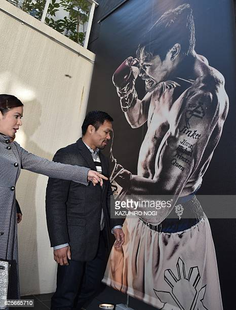 WBO welterweight world champion Manny Pacquiao and his wife Jinkee look at a huge picture of Pacquiao upon their arrival at his boxing gym while MP...