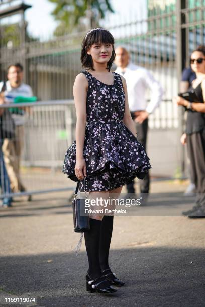 Wen Qi wears a headband a floral print black and purple ruffled dress outside Miu Miu Club 2020 on June 29 2019 in Paris France
