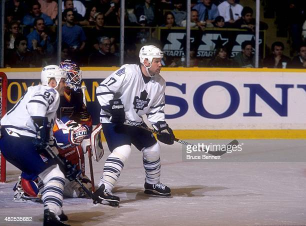 Wendel Clark and Doug Gilmour of the Toronto Maple Leafs set up in front of goalie Grant Fuhr of the St Louis Blues during Game 1 of the Western...