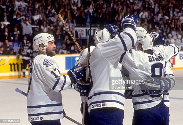 Wendel Clark Bob Rouse and Doug Gilmour of the Toronto Maple Leafs celebrate a goal during a game in the Western Conference Finals against the Los...